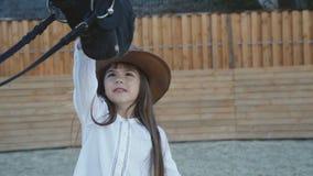 Nettes kleines Mädchen im Hut kommt und streichelt schwarzen Stute ` s Kopf stock video footage