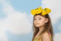 Nettes kleines Mädchen im Kranz des Löwenzahns auf Himmelhintergrund Lizenzfreies Stockfoto