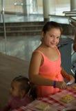Nettes kleines Mädchen im rosa korallenroten Kleid besprühen Pizza mit geriebenem Käse - Kochen, Lebensmittel und Vergnügenskonze Stockfotos