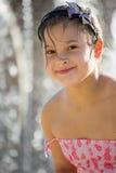 Nettes kleines Mädchen im rosa korallenroten Kleid, das im fontaine spielt Lizenzfreie Stockfotografie