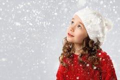 Nettes kleines Mädchen im Winter kleidet auf Schneehintergrund stockfotos