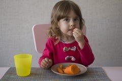 Nettes kleines Mädchen isst Karotte stockbild