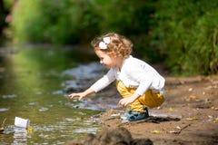 Nettes kleines Mädchen lässt ein Papierboot im Strom laufen stockfotos