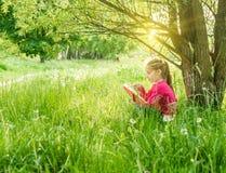 Nettes kleines Mädchen las das Buch stockfotos