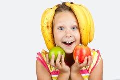Nettes kleines Mädchen mit Äpfeln, Zitrone und Banane wirft positiv auf lizenzfreie stockfotos