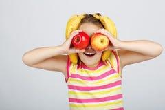 Nettes kleines Mädchen mit Äpfeln, Zitrone und Banane wirft positiv auf stockfotos