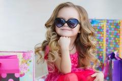 Nettes kleines Mädchen mit bunten Taschen für den Einkauf im Supermarkt Lizenzfreie Stockbilder