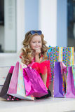 Nettes kleines Mädchen mit bunten Taschen für den Einkauf im Supermarkt Stockfotografie