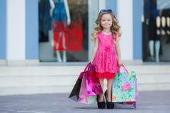 Nettes kleines Mädchen mit bunten Taschen für den Einkauf im Supermarkt Lizenzfreie Stockfotos