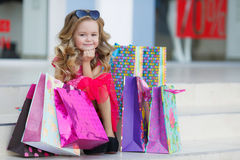Nettes kleines Mädchen mit bunten Taschen für den Einkauf im Supermarkt Lizenzfreies Stockfoto