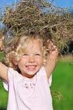 Nettes kleines Mädchen mit dem blonden Haar, das mit Heu spielt Stockbild