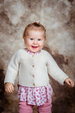 Nettes kleines Mädchen mit dem blonden Haar und den grauen Augen lacht und tanzt Stockbild
