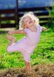 Nettes kleines Mädchen mit dem blonden Spielen des lockigen Haares Stockbild