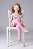 Süßes kleines Mädchen, das auf dem weißen Stuhl, weg schauend sitzt Stockbild