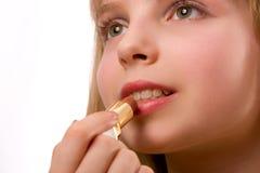 Nettes kleines Mädchen mit dem Lippenstift getrennt auf Weiß Stockbilder