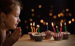 Nettes kleines Mädchen mit dem Parteihut, schauend die Kerzen stockfotografie