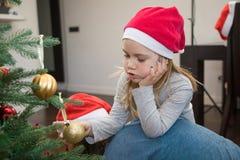 Nettes kleines Mädchen mit dem Sankt-Hut- und -weihnachtsball, der an ihn stillsteht Lizenzfreie Stockfotografie