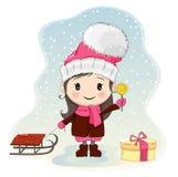 Nettes kleines Mädchen mit dem Schlitten, der nahe Geschenkbox steht und Süßigkeit isst Stockfotografie