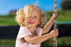 Nettes kleines Mädchen mit den blonden lockigen Haaren Stockfotografie