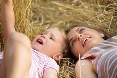 Nettes kleines Mädchen mit der jungen Mutter, die auf dem Weizengebiet liegt Lizenzfreies Stockbild