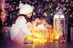 Nettes kleines Mädchen mit Feiertagslaterne nahe Weihnachtsbaum stockfotos