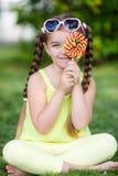 Nettes kleines Mädchen mit großem buntem Lutscher Stockfoto