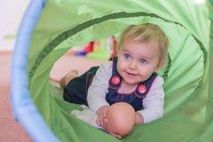 Nettes kleines Mädchen mit ihrer Puppe, die durch den Tunnel kriecht Stockfotografie