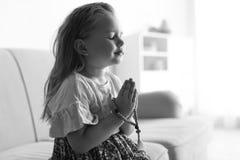 Nettes kleines Mädchen mit Perlen betend auf Sofa im Wohnzimmer, Schwarzweiss-Effekt stockfoto