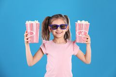 Nettes kleines Mädchen mit Popcorn und Gläsern stockfotos