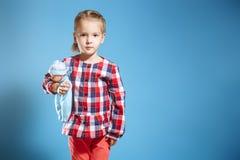 Nettes kleines Mädchen mit Puppe auf blauem Hintergrund stockbild