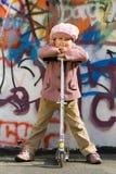Nettes kleines Mädchen mit Roller nahe Graffitiwand Lizenzfreies Stockfoto