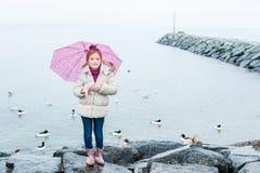 Nettes kleines Mädchen mit rosa Regenschirm Stockfotografie