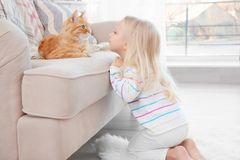 Nettes kleines Mädchen mit roter Katze zu Hause Lizenzfreie Stockfotografie