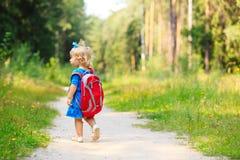 Nettes kleines Mädchen mit Rucksack im Sommerwald Stockfotografie