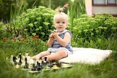 Nettes kleines Mädchen mit Schach im Sommergarten lizenzfreies stockfoto