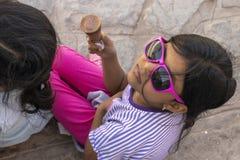 Nettes kleines Mädchen mit Sonnenbrille eine köstliche Eiscreme essend stockfotos