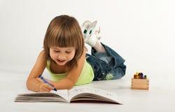 Nettes kleines Mädchen mit Zeichnungsbuch Stockfotografie
