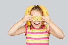 Nettes kleines Mädchen mit Zitrone und Banane wirft positiv herein auf lizenzfreie stockfotos