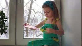 Nettes kleines Mädchen näht eine rosa Handtasche stock video