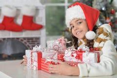 Nettes kleines Mädchen in Sankt-Hut mit Geschenken für Weihnachten zu Hause lizenzfreie stockfotografie
