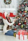 Nettes kleines Mädchen in Sankt-Hut Weihnachtsbaum verzierend stockfotografie