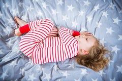 Nettes kleines Mädchen schläft in den pajames auf Bett Lizenzfreie Stockfotografie