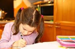 Nettes kleines Mädchen schreibt auf ihr Notizbuch Lizenzfreies Stockfoto
