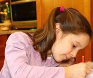 Nettes kleines Mädchen schreibt auf ihr Notizbuch Stockbilder