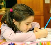 Nettes kleines Mädchen schreibt auf ihr Notizbuch Lizenzfreie Stockbilder