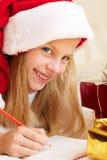 Nettes kleines Mädchen schreibt Santa Claus Brief Lizenzfreies Stockfoto
