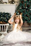 Nettes kleines Mädchen spielt mit Kegeln auf dem Hintergrund des Weihnachtsbaums lizenzfreie stockfotografie
