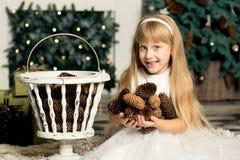 Nettes kleines Mädchen spielt mit Kegeln auf dem Hintergrund des Weihnachtsbaums stockfotografie