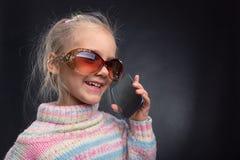 Nettes kleines Mädchen spricht am Telefon Lizenzfreies Stockfoto