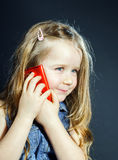 Nettes kleines Mädchen spricht unter Verwendung des neuen Handys Stockfoto